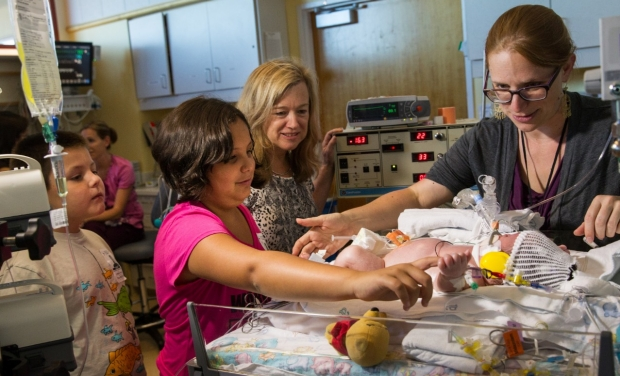 Drs. Krisa Van Meurs and Courtney Wusthoff tend to a pre-ECMO baby as the family looks on, curious.
