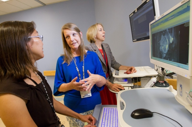 Dr. Valerie Chock talking to Neonatal Nurse Practitioner Diana Kobayashi while Dr. Susan Hintz looks at a computer screen
