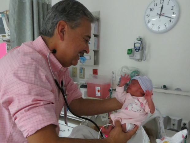 Dr. Bob Castro holding an infant in the Salinas NICU.