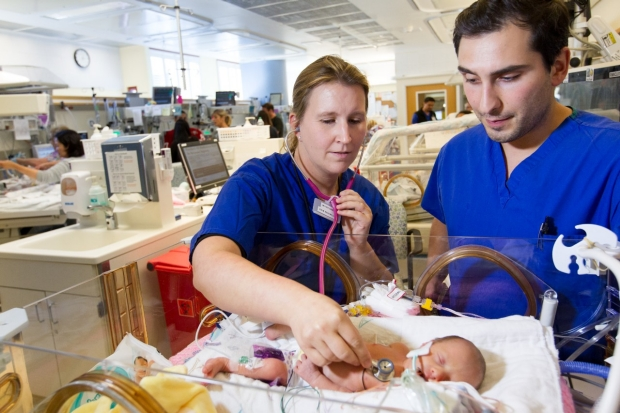Medical students listen to a baby