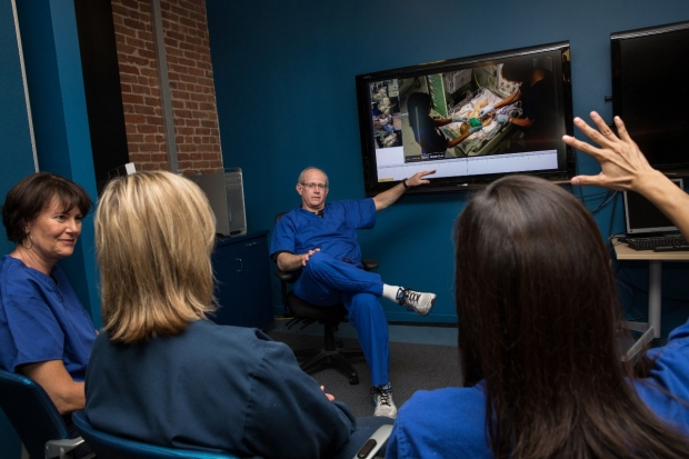 Simulation Debrief at CAPE - Dr. Louis Halamek answers questions while pointing at a screen displaying a recording of the simulation under discussion.