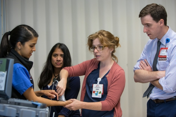 Dr. Laura Peterson trains in point of care ultrasound on Dr. Vidya Pai. Dr. Gregory Goldstein observes the interaction, as instructor Dr. Shazia Bhombal looks on.