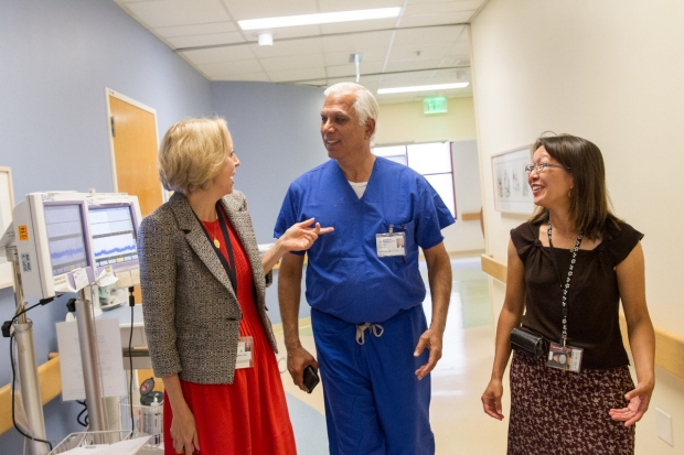 Dr. Susan Hintz talks to Dr. Vinod Bhutani in a hallway while Dr. Valerie Chock looks on.