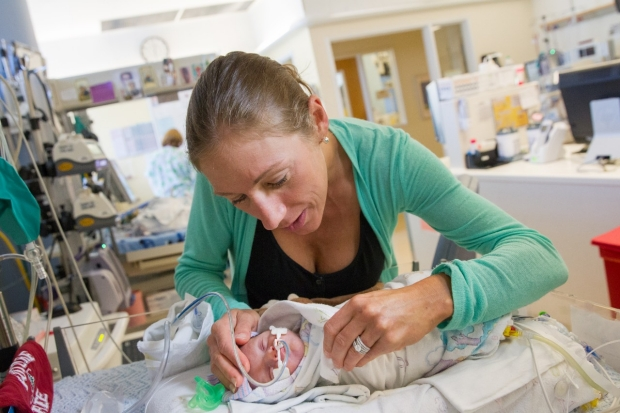 Mother cradles her baby's head as she leans over her bedside.