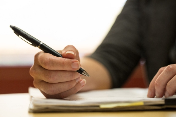 Hand with pen poised over a notepad.