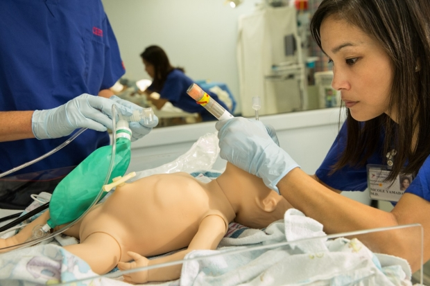 Dr. Nicole Yamada intubates a mannequin baby while another clinician prepares respiratory equipment.