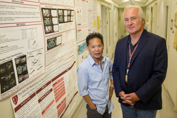 Drs. David Stevenson and Ron Wong posed by posters on their work.