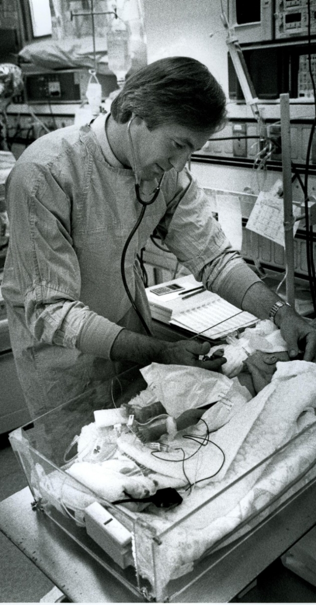 A black and white photo of Dr. David Stevenson caring for infant in the NICU in the 1980s