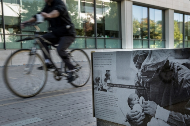 Person riding a bicycle past a marker on the Stanford School of Medicine history walk detailing significant milestones at Stanford in the field of neonatology.